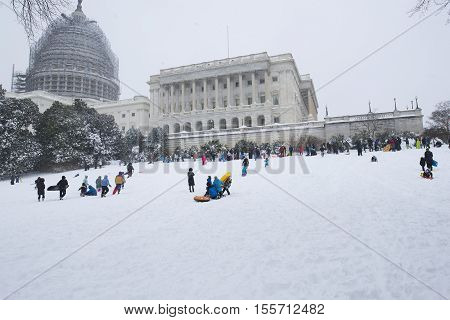 Washington D.C. USA - January 23 2016: People ride with a snow slide in a snowstorm near Capitol.