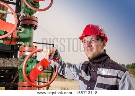 Oil field worker near wellhead valve wearing red helmet and work clothes holding wrench in his hands. Oil and gas concept.