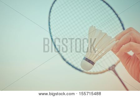 shuttlecocks on hand and racket badminton with blue sky background