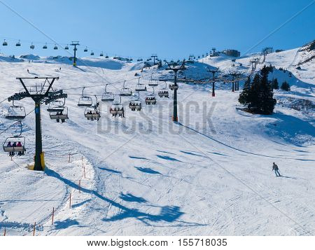 Ski lift and ski slope with skiers under it on sunny winter day with blue sky. Alpine resort Silvretta Arena near Samnaun and Ischgl, Switzerland and Austria, Alps, Europe