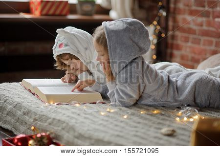 Christmas Holidays. Two children lie on a bed in soft pyjamas. Bedroom is decorated by christmas garlands. The children read a great book with Christmas tales. Christmas - magic time. Merry Christmas.