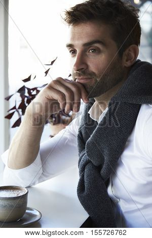 handsome Man daydreaming over coffee in cafe