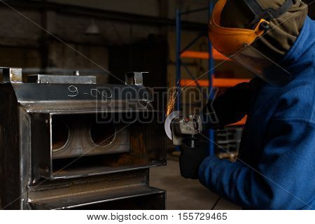 Man in blue solders black solid fuel boiler