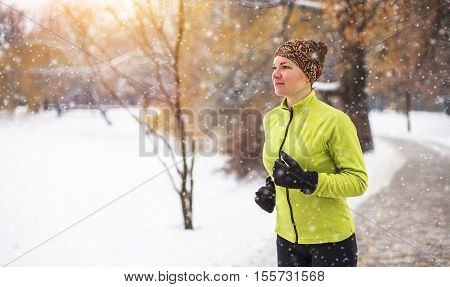 Young sport woman doing exercises during winter training outside in cold snow weather.