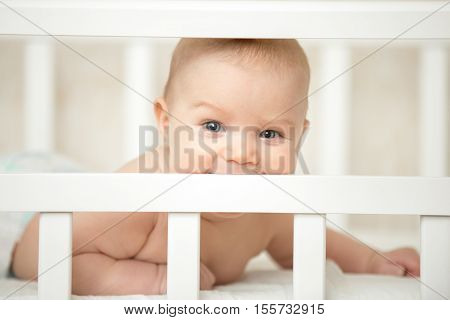 Cute Child Looking Interested Through The Frame Of Baby Crib
