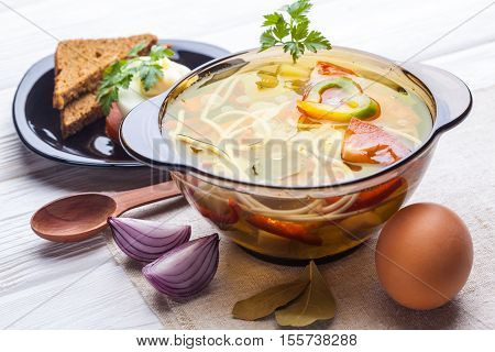 Fresh vegetable soup with noodles in a pot on the white wooden background