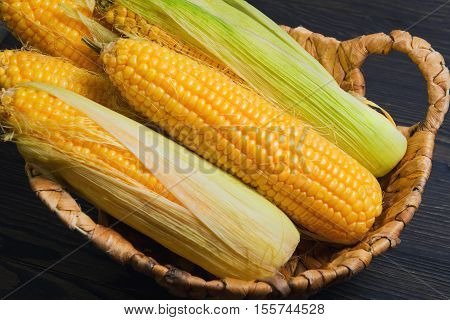 Fresh corn on the cob in wicker basket on brown wooden table. Purified corn cobs. Untreated corn cobs.