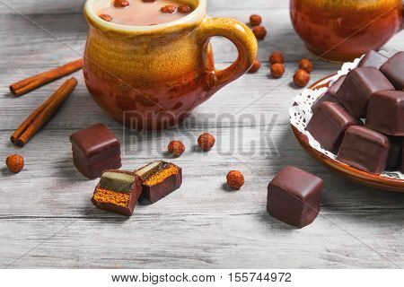 Traditional German domino stein chocolate gingerbread cakes with marzipan and jelly filling. Hot chocolate cocoa two cups. Chocolate balls for domino stein gingerbread and hot chocolate.