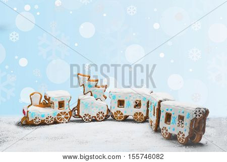 Gingerbread Cookies in the form of train. Christmas cookies train covered with icing. Christmas Holidays sweets Gingerbread Cookies train. New Year card with snow Christmas gingerbread cookies train