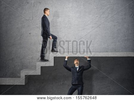 Businessman climbs the concrete stairs, which the other person keeps. Go over the heads. Do anything for the sake of personal gain. Social inequality. Boss.