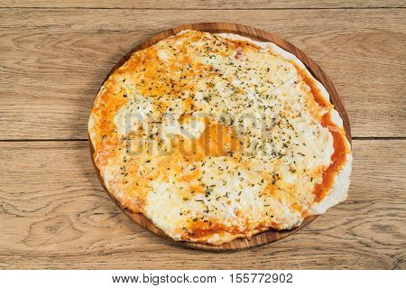 Cheese Italian pizza with a whole egg yolk in the middle, served on a wooden plate