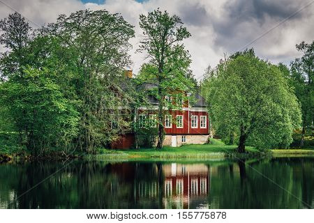 Swedish red and white house standing close by the lake in a very lush environment.