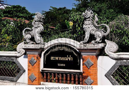 Chiang Mai Thailand - December 31 2012: Two mythical stone dragons decorate a small roadway bridge over a klong (canal)