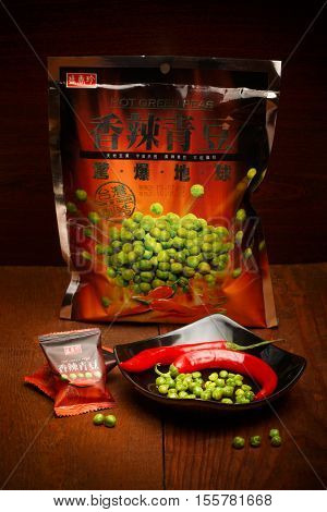 KYIV UKRAINE - JANUARY 19 2016. Editorial photo of Hot Green Peas snack with red chilli pepper by Triko Sheng Xiang Zhen Taiwanese company at wooden background. Shallow dof. Focus on peas in dish.