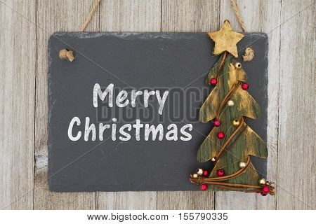 Old fashion Merry Christmas greeting A retro chalkboard with a rustic primitive Christmas tree hanging on weathered wood background with text Merry Christmas