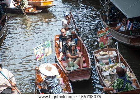 RATCHABURI THAILAND-SEPTEMBER 28: Damnoen Saduak Floating Market on September 282016 in Thailand. Having many small boats laden with Souvenir shop colourful fruits vegetables and Thai cuisine.
