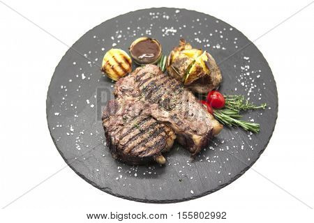 Juicy beef steak medium rare on a stone plate with cherry tomatoes and a large sea salt.