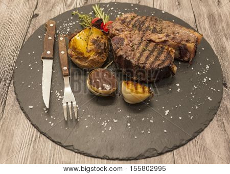 On wooden table background juicy beef steak medium rare on a stone baked potatoes and barbecue sauce and large sea salt with fork and knife