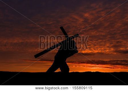 Man carrying a cross on his back with a dawn clouded sky in the background.