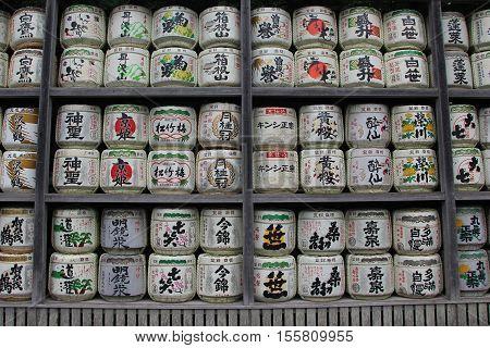 Kamakura, Japan - September 10, 2013: Barrels of sake called nihonshu donated to the Shinto Shrine,  Tsurugaoka Hachimangū  in Kamakura, Japan. Japanese donate sake to the shrines as offering for the Gods.