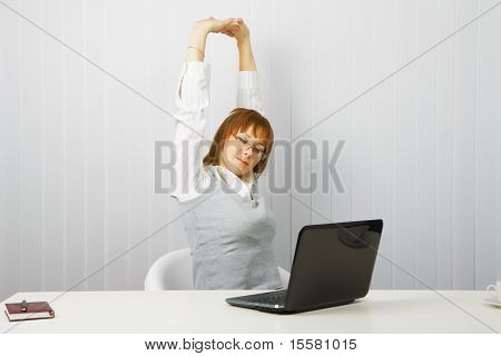 Tired Girl With A Laptop Stretches