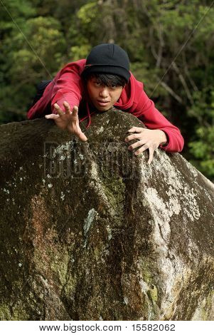 Man reaching out arm over rock