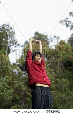 Happy asian man stretching arms outdoors