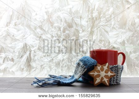 red mug with a warm scarf and pastries in the background of a winter window / warming holiday mood
