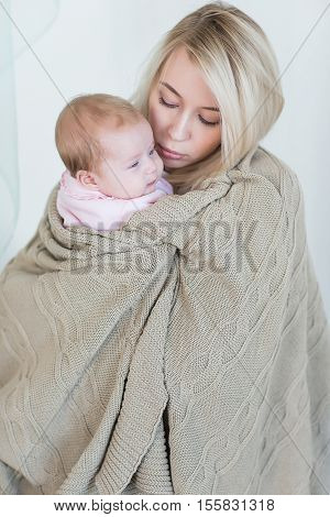 Young beautiful mother comforts, so as not to cry her infant daughter. motherhood concept, love and care.