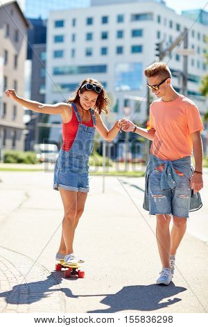 summer holidays, extreme sport and people concept - happy teenage couple riding short modern cruiser skateboard on city street