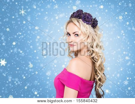 Beauty portrait of attractive blond girl with curly hair and a beautiful headband over blue winter background. Christmas concept.