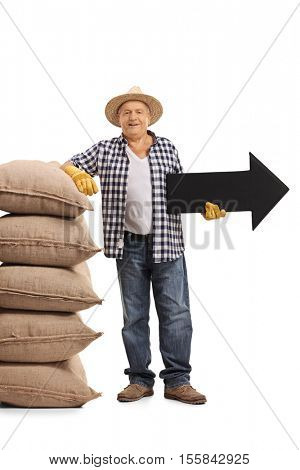 Full length portrait of a mature farmer leaning on a pile of burlap sacks and holding an arrow pointing right isolated on white background