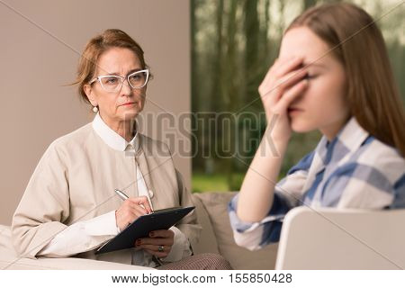 Probation Officer Taking Notes While Talking With Teenager