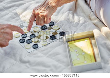 Senior citizens compete on a board game in summer in the garden
