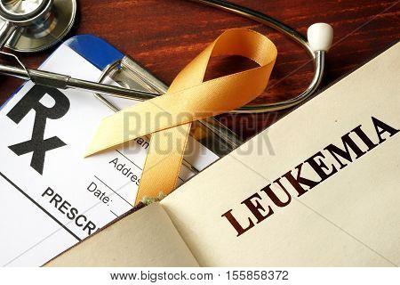 Leukemia written on a page and  orange awareness ribbon.