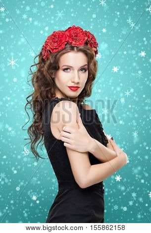 Beautiful brunette with bright red flower headband over green winter background. Christmas concept.