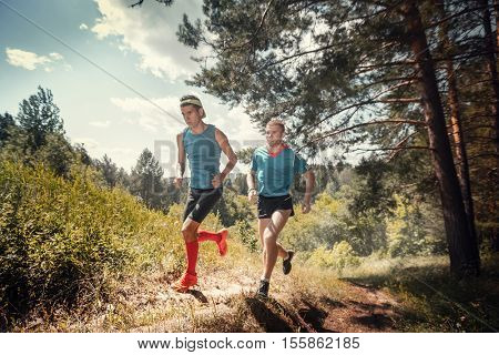 Trail running athletes crossing off road terrain at sunny day