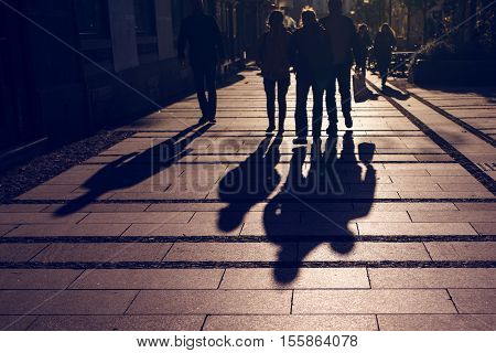 Silhouettes of people walking on city street and casting shadows on pavement general public concept for any community related theme.