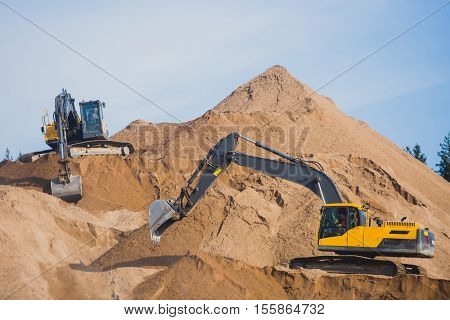 Yellow heavy excavator and bulldozer excavating sand and working during road works, unloading sand and road metal during construction of the new road