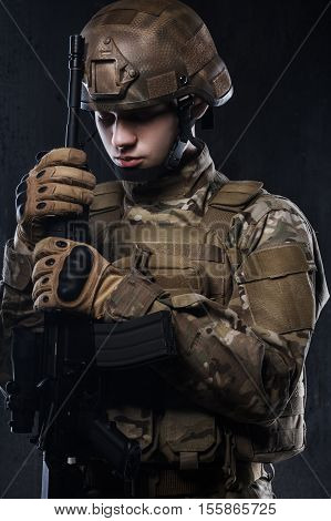 Defeat in a difficult fight. Special forces soldier on dark background.