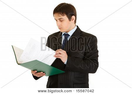Concentrated modern businessman holding folder and checking documents isolated on white
