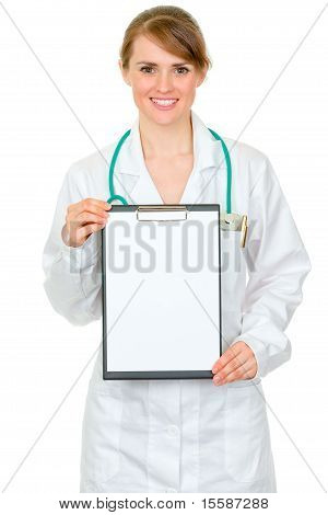 Smiling medical doctor woman holding blank clipboard in hands isolated on white