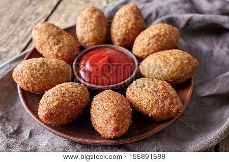 Kibbeh traditional middle eastern oriental restaurant lamb meat stuffed and bulgur kofta spicy meatball croquettes food on vintage wooden table background