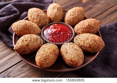 Kibbeh traditional homemade middle eastern beef, lamb, goat or camel meat stuffed bulgur kofta spicy meatball fried croquettes dinner food on rustic wooden table background