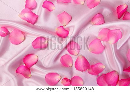sweet pink roses petal on soft pink silk fabric romance and love card concept
