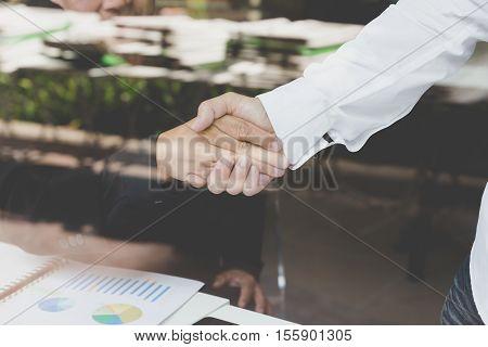 businessman handshaking in office - teamwork cooperation agreement acquisition concept - seen through glass shot