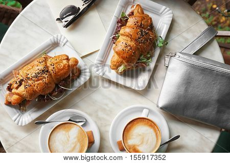 Breakfast with croissant sandwiches and coffee on table