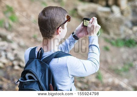 man with a backpack photographed on a photocamera natural landscape