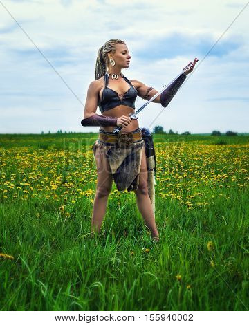 Beautiful athletic woman in the image of an ancient warrior woman on a background summer nature.