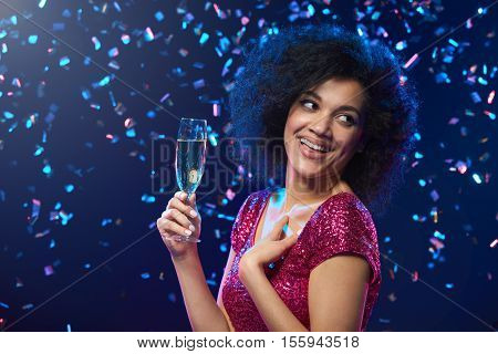 Party, drinks, holidays and celebration concept. Closeup of happy mixed race woman in sequined dress with glass of sparkling wine over colorful background with confetti looking to the side at blank copy space